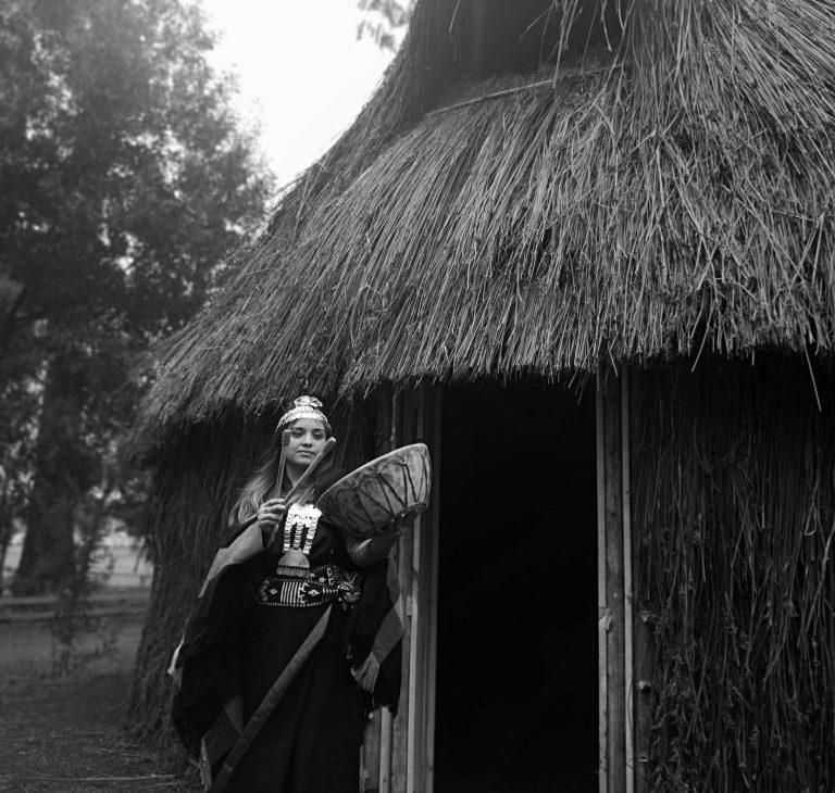 FOTO GANADORA EN CATEGORÍA COSTUMBRES - Fotografía en blanco y negrode Mapuche mujer tocando instrumento musical